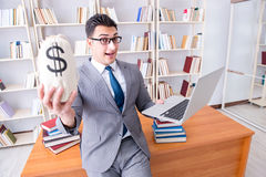 The businessman in library with a money sack and a laptop Stock Photography