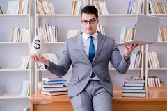 The businessman in library with a money sack and a laptop Royalty Free Stock Photography