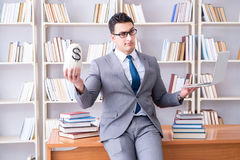 The businessman in library with a money sack and a laptop Royalty Free Stock Images