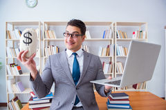 The businessman in library with a money sack and a laptop Stock Images