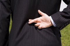 Businessman lie. A businessman telling a lie with the fingers crossed Royalty Free Stock Photo