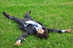 Businessman lies on back on grass Stock Photo
