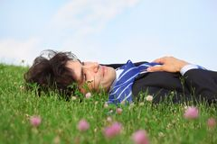 Businessman lies on back on grass with closed eyes Royalty Free Stock Photography