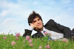 Businessman lies on grass with closed eyes Royalty Free Stock Photography