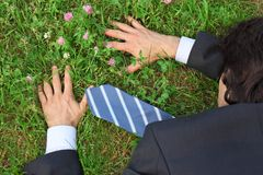 Businessman lies prone on grass, top view Stock Photos