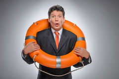 Businessman with a life buoy. Surprised businessman standing wit Stock Photography