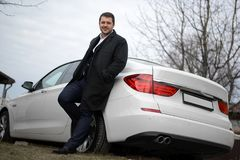 A businessman is standing by his car royalty free stock image
