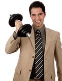 Businessman lifting a dumbbell. Young male businessman in light suit with power lifts a dumbbell and shows strength and determination, isolated against white royalty free stock image