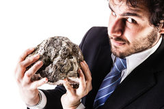 Businessman lifting a heavy rock Royalty Free Stock Photography