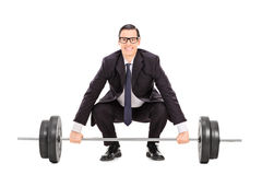 Businessman lifting a heavy weight stock photography
