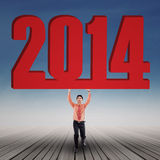 Businessman is lifting new year 2014 outdoor Stock Photo