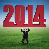 Businessman is lifting new year 2014. Portrait of businessman is lifting new year 2014 on the meadow Stock Illustration