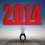 Businessman lifting new year 2014 under blue sky Royalty Free Stock Photos
