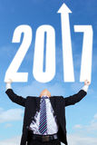 Businessman lifting number 2017 Royalty Free Stock Photo