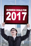 Businessman lifting up a board with a text. Image of happy businessman lifting up a board with a text of business goals for 2017 Stock Photos