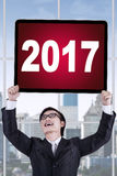 Businessman lifting up numbers 2017 on a board Stock Photos