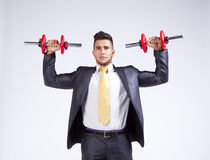 Businessman lifting weights. Strong businessman lifting heavy weights stock photography