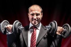 Businessman lifting weights Stock Photos