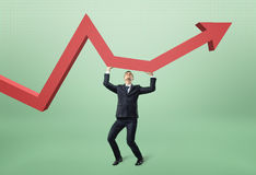 Businessman lifts red arrow up. Royalty Free Stock Photo