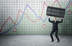 Businessman lifts up barrel of oil on background with rising graph. Royalty Free Stock Photos