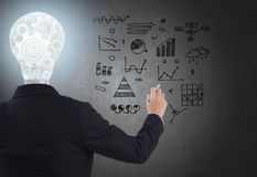 Businessman with lighbulb in head standing and hand drawing. stock photos