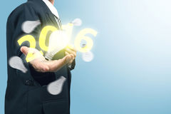 Businessman with light bulb and number 2016. New year Royalty Free Stock Photo