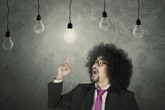 Businessman with light bulbs. Aha Moment: Businessman with glowing light bulb Stock Photography