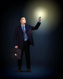 Businessman with light shining. Young successful businessman holding a shining light in his hand as a symbol of success and advancement Royalty Free Stock Photo