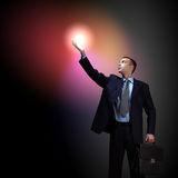 Businessman with light shining Stock Photo