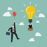 Businessman in lightbulb balloon fly pass businessman with red balloon. Stock Image