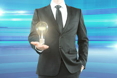 Businessman with lightbulb blue background Royalty Free Stock Photography