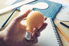 Businessman with lightbulb on desk in workplace.Ideas,creativity. Inspiration and start up concept Stock Photos