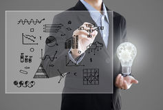Businessman with lightbulb and hand drawing graph inspiration . Royalty Free Stock Photos