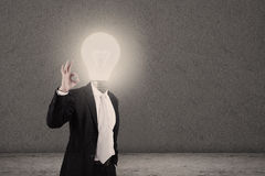 Businessman with lightbulb head and OK sign Stock Image