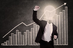 Businessman with lightbulb head raised hand. With blackboard Royalty Free Stock Image