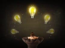 Businessman with lightbulbs over his head Stock Photos
