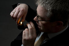 Businessman lighting up tobacco pipe Stock Images