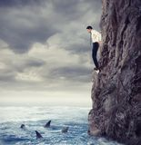 Businessman is likely to fall into the sea with shark. Risks and difficulties concept Stock Photos
