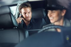Businessman in limousine chauffeur driving stock photo