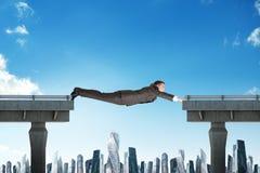 Businessman linking broken bridge. Above city scape Royalty Free Stock Photography