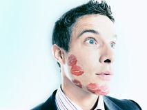 Businessman Lipstick Kiss Marks Over Face Stock Photo