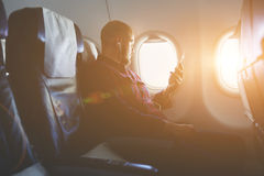 Businessman is listening audio book via mobile phone during flying in an airplane royalty free stock image