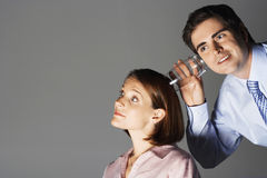 Businessman Listening Through Glass To Woman's Head Stock Photo
