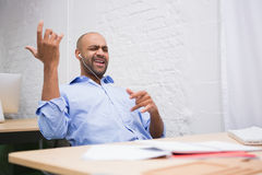 Businessman listening music while playing air guitar in office Royalty Free Stock Photo