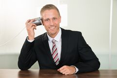 Businessman listening from tin cans phone. Young Businessman Listening From Tin Cans Phone At Desk Royalty Free Stock Image
