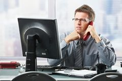Businessman listening to landline call in office. Focused businessman listening to explanation of computer report on landline phone looking at screen sitting in Stock Photo