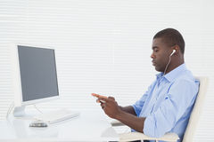 Businessman listening to music while he works Royalty Free Stock Photo