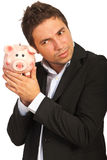 Businessman listening to piggy bank Royalty Free Stock Photography