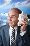 Businessman listening to the shell. And ocean behind him Stock Photo