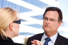 Businessman Listens to Female Colleague Stock Photo